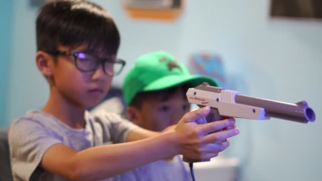 modern asian kids with old/retro nintendo video games - slow motion - toy gun stock videos & royalty-free footage