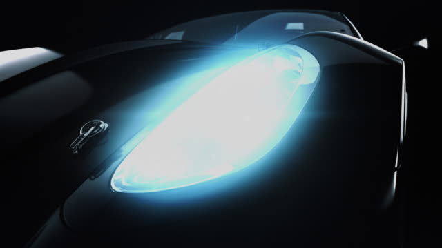 modern black metallic car in spotlight. - headlight stock videos & royalty-free footage