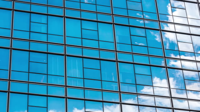 modern blue building with glass wall  in blue sky.timelapse - wall building feature stock videos & royalty-free footage