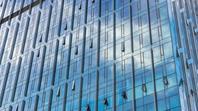 modern blue building with glass wall  in blue sky.timelapse - low angle view stock videos & royalty-free footage