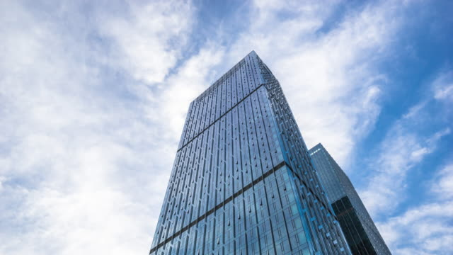 modern blue building with glass wall  in cloud sky.timelapse
