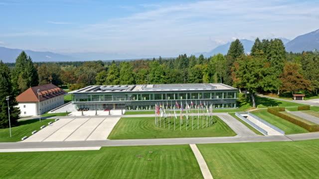 vídeos de stock, filmes e b-roll de edifício moderno aéreo de um centro de congressos - kranj