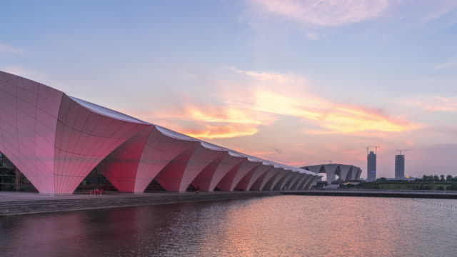 modern building with abstract roof near water in shanghai at twilight. timelapse day to night