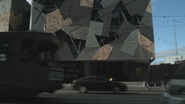 MS PAN Modern buildings at Federation Square, traffic on street in foreground, Melbourne, Victoria, Australia