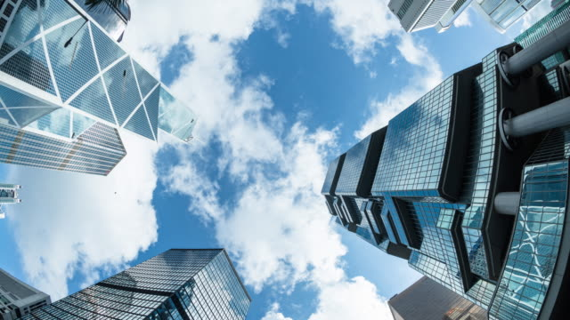 Modern business buildings with blue sky, time lapse 4k, tilt down.