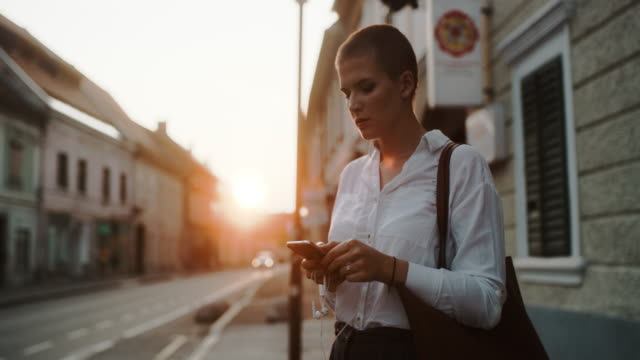 ms modern business woman using a smartphone in the city at dusk - after work stock videos & royalty-free footage