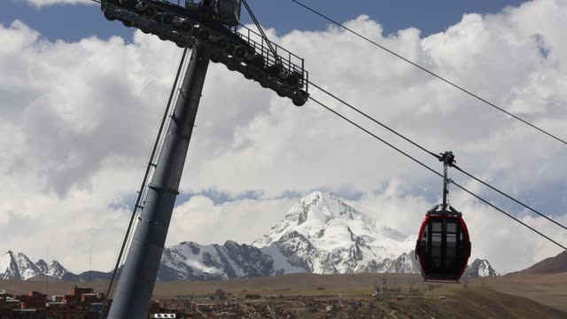 a modern cable car system in la paz, bolivia with the peak of huayna potosi in the background whose glaciers are melting rapidly due to climate change. - la paz region la paz stock-videos und b-roll-filmmaterial