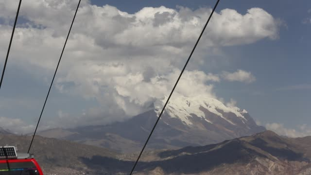 a modern cable car system in la paz bolivia with the peak of illimani in the background whose glaciers are melting rapidly due to climate change - la paz region la paz stock-videos und b-roll-filmmaterial