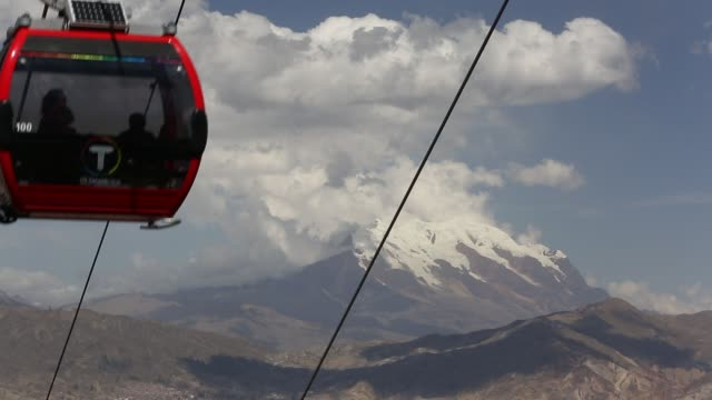 a modern cable car system in la paz, bolivia with the peak of illimani in the background whose glaciers are melting rapidly due to climate change. - la paz region la paz stock-videos und b-roll-filmmaterial