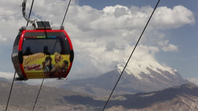 A modern cable car system in La Paz, Bolivia with the peak of Illimani in the background whose glaciers are melting rapidly due to climate change.