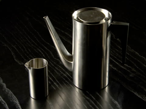 Modern chrome coffee pot and creamer displayed on black wooden table
