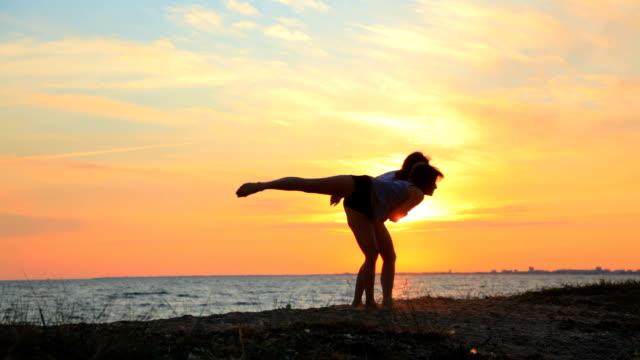 モダンでコンテンポラリーなダンスの若い女子体操夕暮れのビーチ - アスレチック点の映像素材/bロール