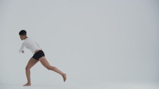 vidéos et rushes de modern dancer dancing in studio, jumping and flipping mid air - souplesse