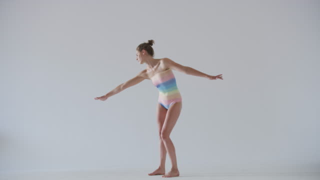 modern dancer dancing in studio wearing rainbow leotard - gymnastikanzug stock-videos und b-roll-filmmaterial