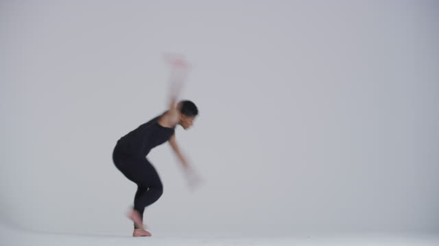 modern dancer woman back flipping and dancing in studio dressed in black - white background stock videos & royalty-free footage