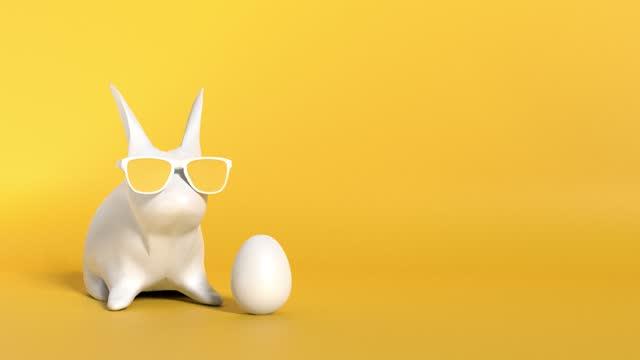 moderne osterhase tragen brille mit einem weißen ostereier auf gelbem hintergrund in 4k-auflösung - happy easter stock-videos und b-roll-filmmaterial