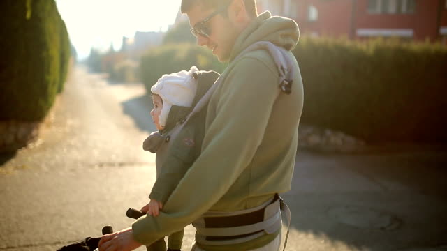 modern father carrying baby - baby carrier stock videos & royalty-free footage