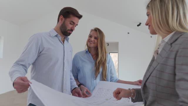 vídeos de stock, filmes e b-roll de arquiteta moderna mostrando o projeto da casa para novos donos de casas - new