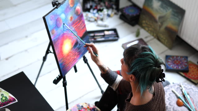 modern female painter working on her art project from her workshop - cross legged stock videos & royalty-free footage