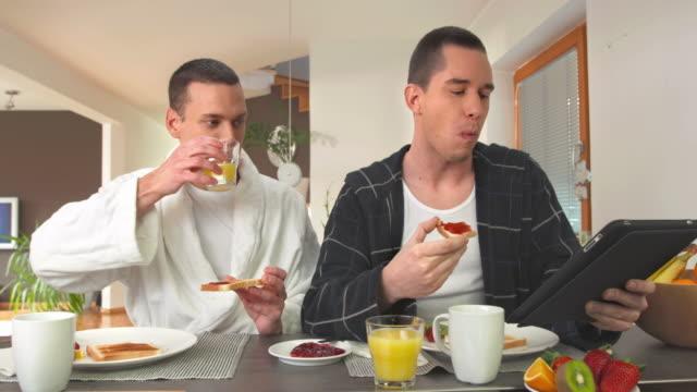 vídeos de stock, filmes e b-roll de hd dolly: moderno gay casal comendo café-da-manhã - homem homossexual