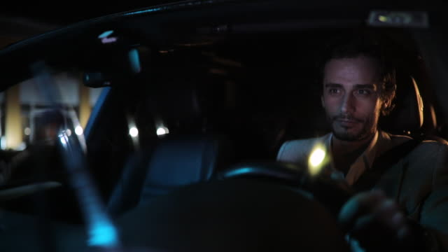 modern gentleman driving a car on a rainy night - chauffeur stock videos and b-roll footage