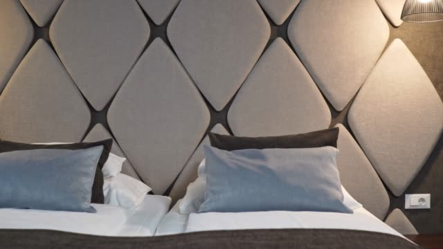 modern geometric design head bed in a hotel room - tidy room stock videos & royalty-free footage