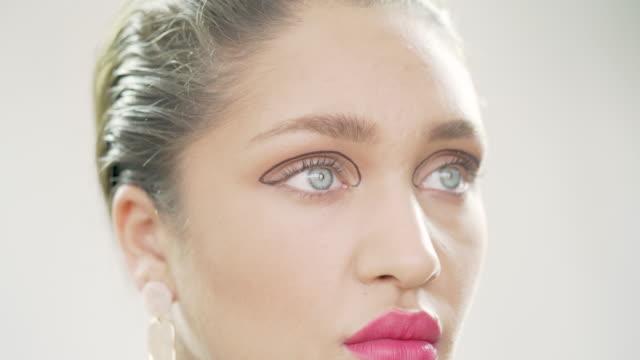 スタジオでモデルの顔に現代の幾何学的アイライナー - ビフォーアフター点の映像素材/bロール
