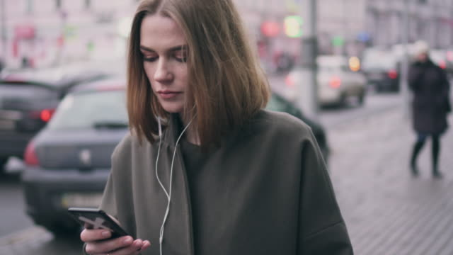 modern girl using phone and headphones while walking on street - ascoltare video stock e b–roll