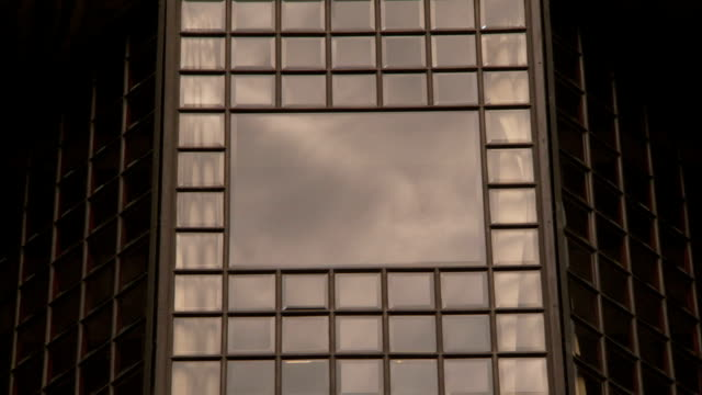 A modern glass building reflects drifting clouds. Available in HD