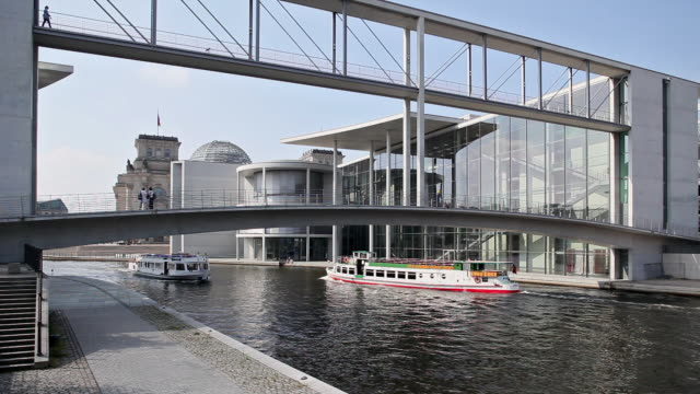 ws modern government buildings and tour boat on river spree, berlin, germany - parliament building点の映像素材/bロール