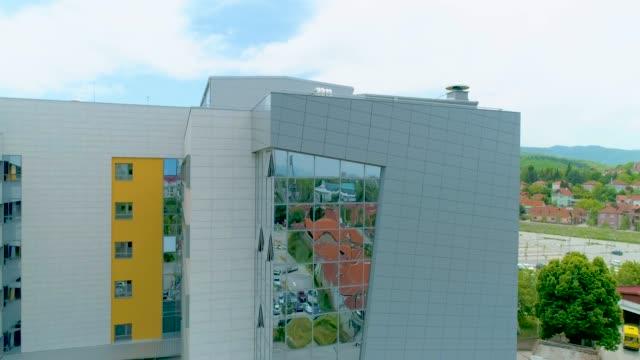 moderno edificio ospedaliero con video aereo sullo skyline della città - parking video stock e b–roll