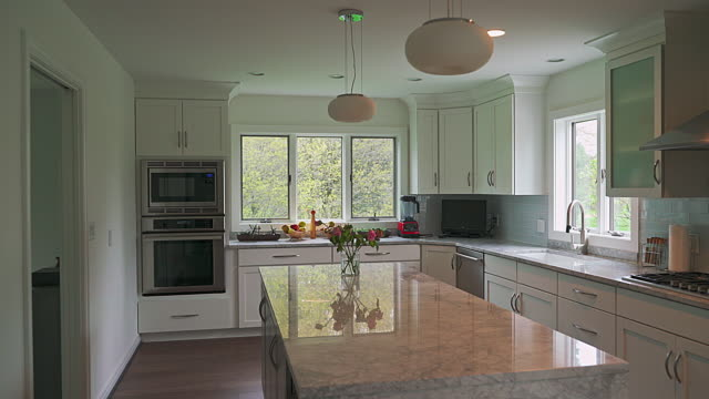 modern kitchen interior in the luxury residential house, with wide windows and natural light. the camera moving forward and ending looking through the window onto the backyard. - flat stock videos & royalty-free footage