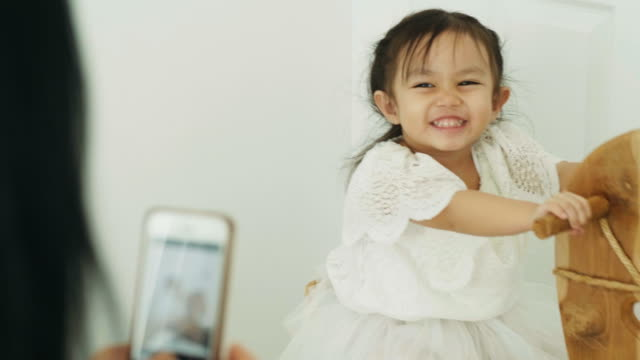 modern life of thai mother and her daughter are taking picture by using smart phone at their bedroom for leisure activity -relative of mother and her baby with mother's day concept - photographing stock videos and b-roll footage