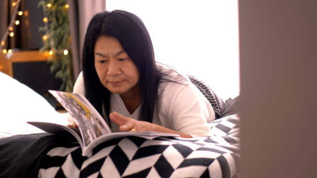modern lifestyles of thai senior adult hipster is reading book for her leisure activity at her bedroom - magazine stock videos & royalty-free footage