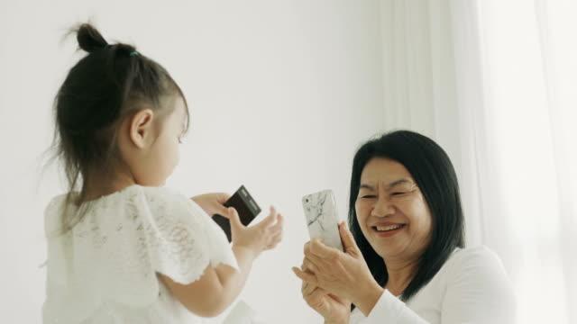 タイ人の母親と娘の寝室にスマート フォンを使用して、写真を撮る間の技術概念と現代のライフ スタイル - カメラ点の映像素材/bロール
