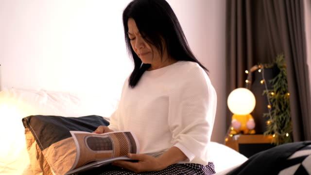 現代生活方式與泰國資深婦女, 當讀書在她的臥室裡為放鬆 - looking away 個影片檔及 b 捲影像