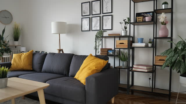 modern living room with grey couch and industrial design shelves - domestic room stock videos & royalty-free footage