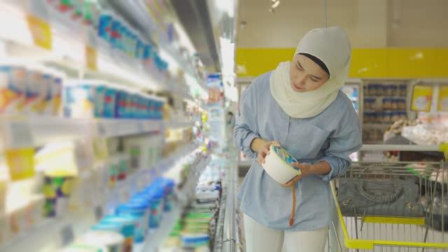 stockvideo's en b-roll-footage met moderne maleisische vrouw met hijab en bescheiden kleding die bij gekoelde sectie in supermarkt tijdens weekend kopen - dairy product