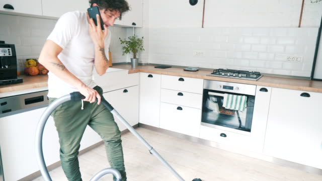 modern man cleaning the house. - vacuum cleaner stock videos & royalty-free footage