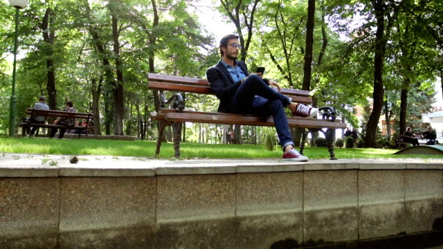 modern man in park - bench stock videos & royalty-free footage