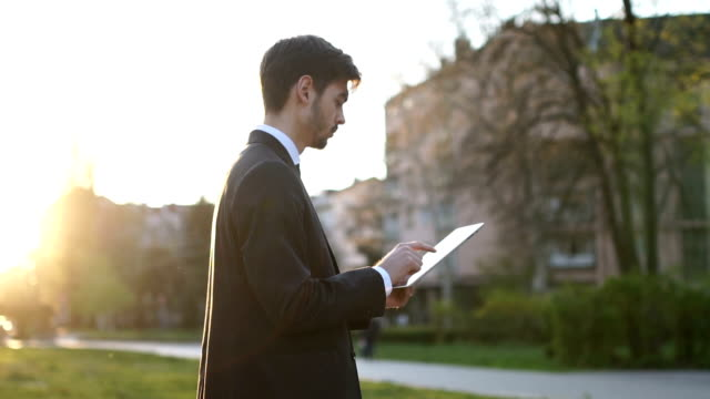 vídeos de stock e filmes b-roll de modern man outdoors using tablet - dia