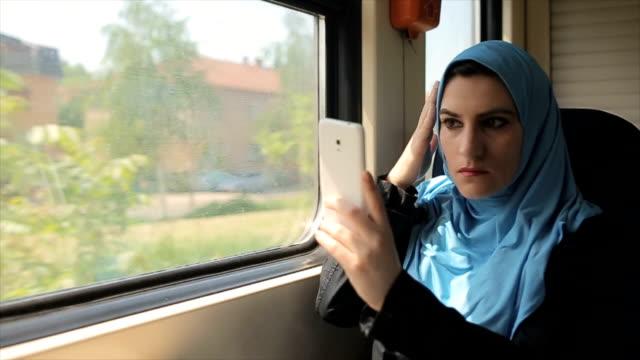 現代成熟したイスラム教徒の女性が電車の中の携帯電話で selfie を取る - モデスト・ファッション点の映像素材/bロール