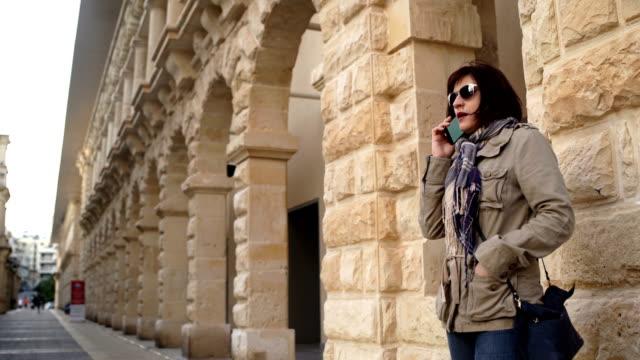 vídeos de stock, filmes e b-roll de mulher envelhecida média moderna que fala no telefone móvel - ponto turístico