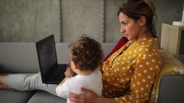 vídeos de stock, filmes e b-roll de mãe moderna trabalhando em casa com seu filho - almofada