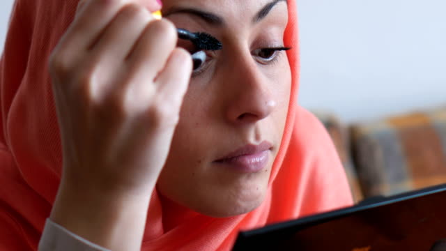 stockvideo's en b-roll-footage met moderne moslimvrouw make-up toe te passen - hoofddoek