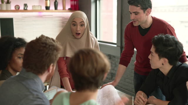 Modern Muslim woman wearing hijab lead the business meeting with multi-ethnic group of people. Explaining the project.
