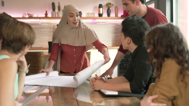 Modern Muslim woman wearing hijab lead the business meeting with multi-ethnic group of people. Unrolling the drawings.