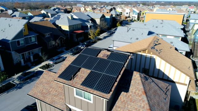vídeos de stock e filmes b-roll de modern neighborhood with lots of solar panels and clean renewable energy savings in austin , texas aerial drone view - painel solar