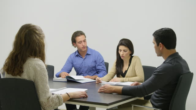 ws modern office interior group of people (two men, two women) in glass-enclosed meeting room seated at table lookingt at documents in front of them - 2k resolution stock videos and b-roll footage