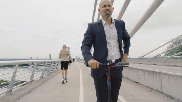 stockvideo's en b-roll-footage met slo mo moderne bureauarbeider die zijn smartphone controleert terwijl het berijden van een elektrische scooter - mid volwassen mannen